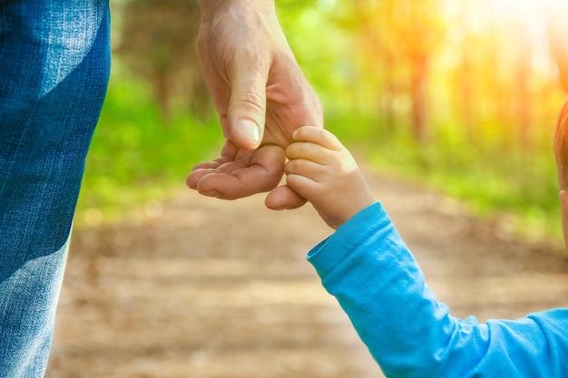 Der elternteil hält die hand des kindes