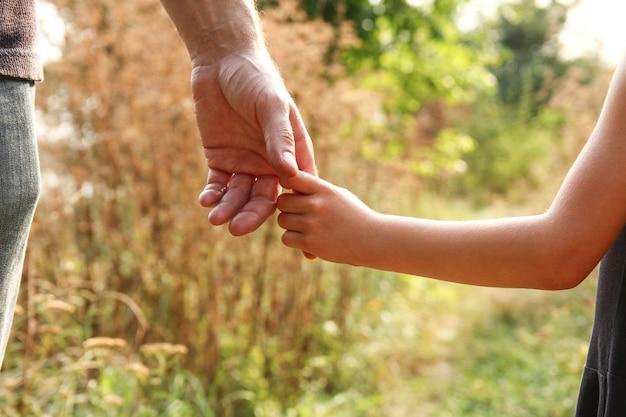 Der elternteil hält die hand eines kleinen kindes