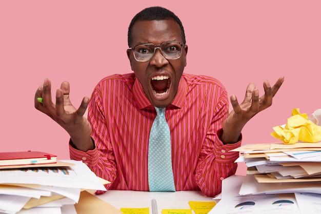 Der empörte schwarze besitzer einer handelsfirma hält die hände in genervter geste, schreit vor wut, öffnet den mund weit und trägt ein formelles outfit