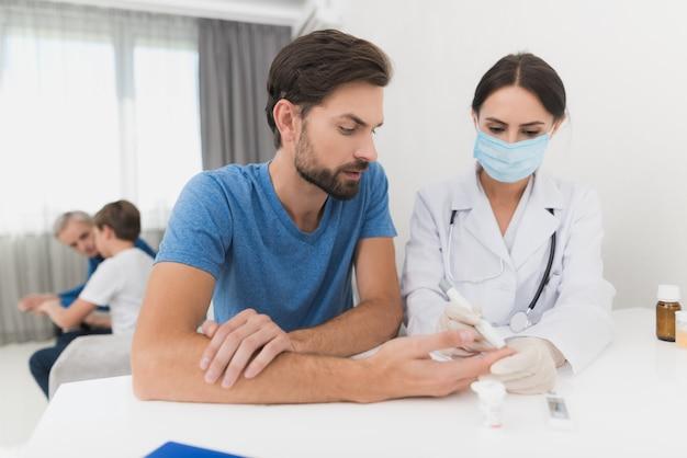 Der endokrinologe misst den zuckergehalt im blut.