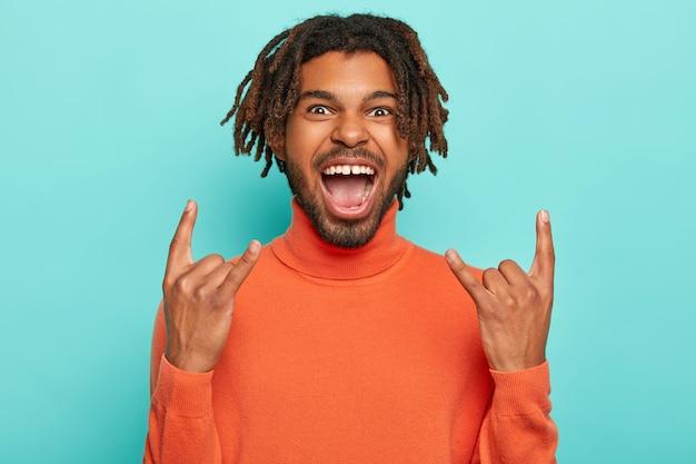 Der energiegeladene dunkelhäutige junge mann rockt auf der party, bringt positive stimmung, zeigt rock'n'roll-geste, hält den mund offen, hat dreadlocks, trägt einen orangefarbenen rollkragenpullover, isoliert über blauem hintergrund.