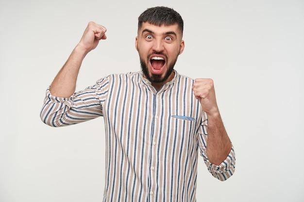 Der energiegeladene junge attraktive dunkelhaarige bärtige mann, der mit großen augen und geöffnetem mund aufgeregt aussieht und glücklich seine hände hebt, während er über der weißen wand steht