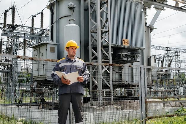 Der energietechniker inspiziert die ausrüstung des umspannwerks. energietechnik. industrie.