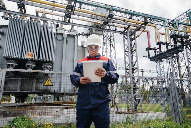 Der energietechniker inspiziert die ausrüstung des umspannwerks