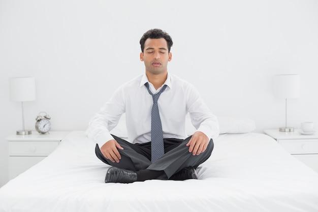 Der entspannte gut gekleidete mann, der mit augen sitzt, schloss auf bett