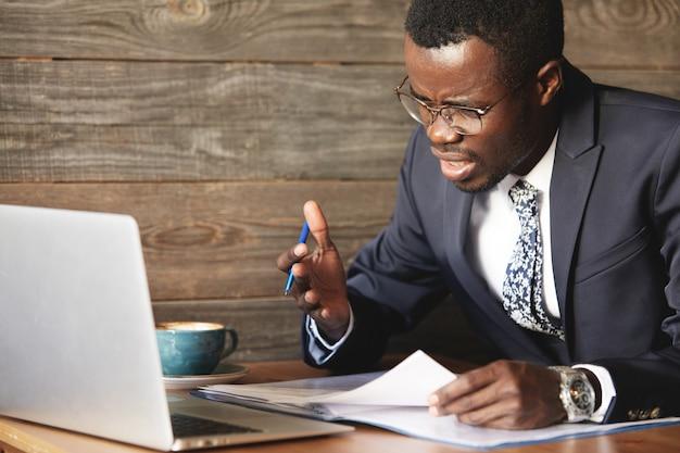 Der enttäuschte afrikanische geschäftsmann ist durch einen fehler in offiziellen dokumenten benommen und verwirrt