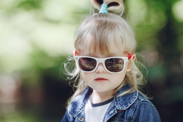 Der entzückende kleine mädchen mit sonnenbrille posiert