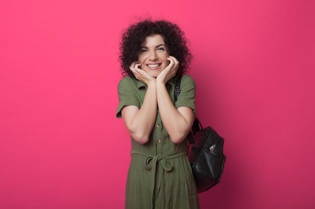 Der entzückende student mit den lockigen haaren lächelt und betrachtet die kamera, die eine tasche an einer roten wand hält