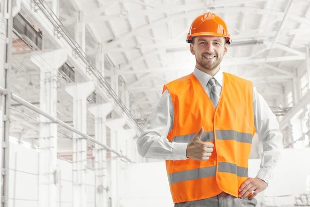 Der erbauer im orangefarbenen helm gegen industrie