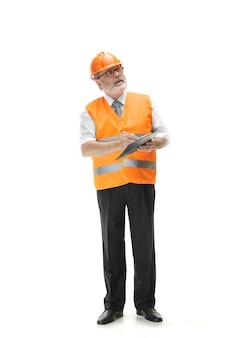 Der erbauer in einer bauweste und in einem orangefarbenen helm, der auf weißem studiohintergrund steht. sicherheitsfachkraft, ingenieur, industrie, architektur, manager, beruf, kaufmann, berufskonzept