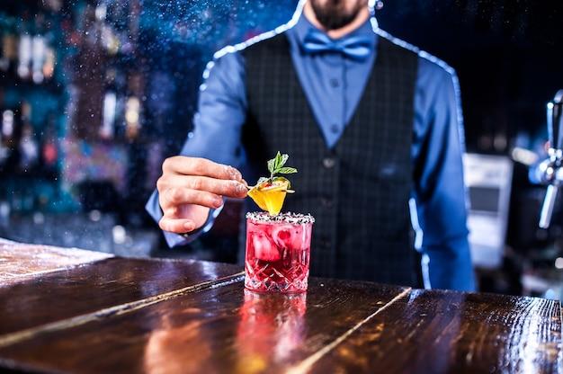 Der erfahrene barkeeper demonstriert seine fähigkeiten im nachtclub über den ladentisch