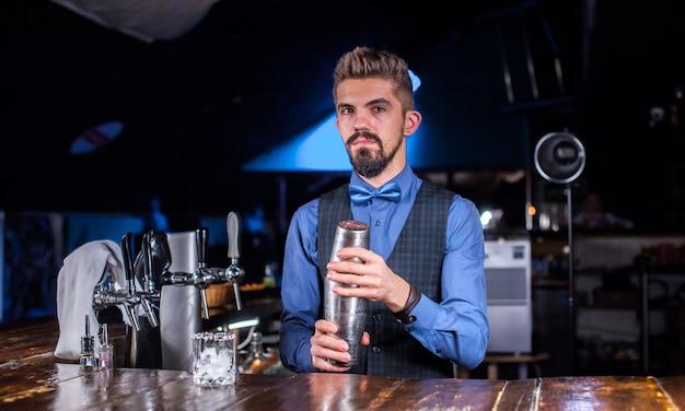 Der erfahrene barmann demonstriert den prozess der zubereitung eines cocktails, während er in der kneipe in der nähe der theke steht