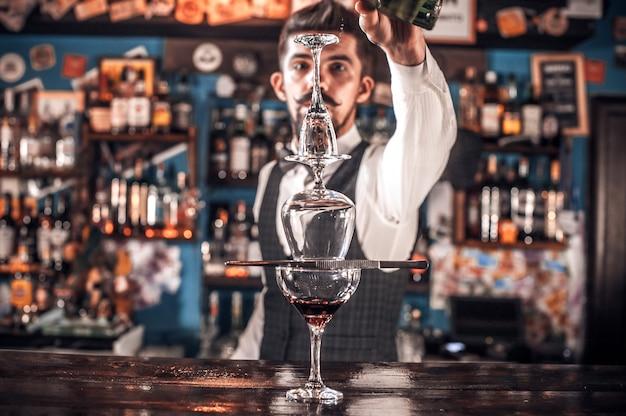 Der erfahrene barmann formuliert einen cocktail in der kneipe