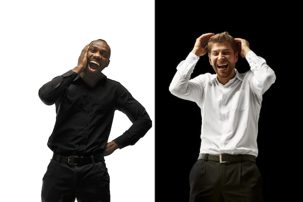 Der erfolg glücklich afro und kaukasische männer. gemischtes paar. dynamisches bild von männlichen modellen auf weißem und schwarzem studio. konzept der menschlichen gesichtsgefühle.