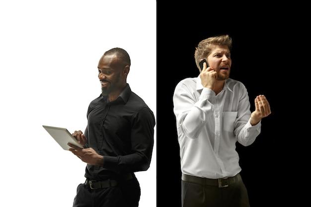 Der erfolg glücklich afro und kaukasische männer. gemischtes paar mit gerät. dynamisches bild von männlichen modellen auf weißem und schwarzem studio. konzept der menschlichen gesichtsgefühle.
