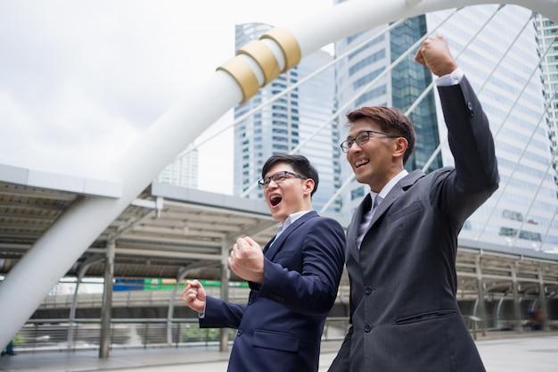 Der erfolg mit zwei geschäftsleuten zeigt sich zuversichtlich und glücklich, nachdem der verkauf fortgesetzt wurde.