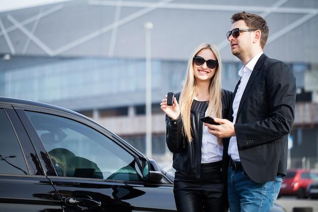 Der erfolgreiche besuch beim händler. glückliches junges paar wählt und kauft ein neues auto für die familie