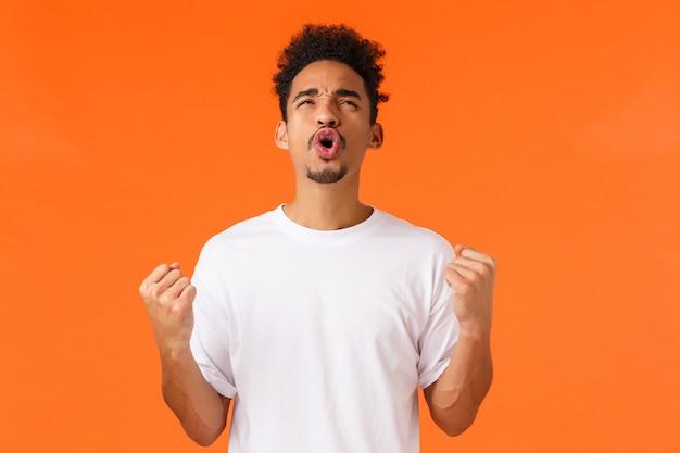 Der erleichterte und aufgeregte triumphierende afroamerikaner, der glücklich sich fühlt, erzielen erfolg und werden meister, faustpumpe, die ja schreit und den erfüllten himmel schaut, orange