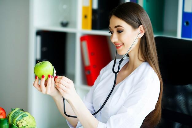 Der ernährungsberater hält in den händen von fresh green apple.