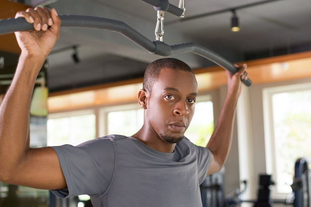 Der ernste schwarze mann, der auf lat trainiert, ziehen maschine herunter