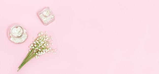 Der erste frühling blüht maiglöckchen und eine glasflasche mit getrockneten blütenblättern für die aromatherapie