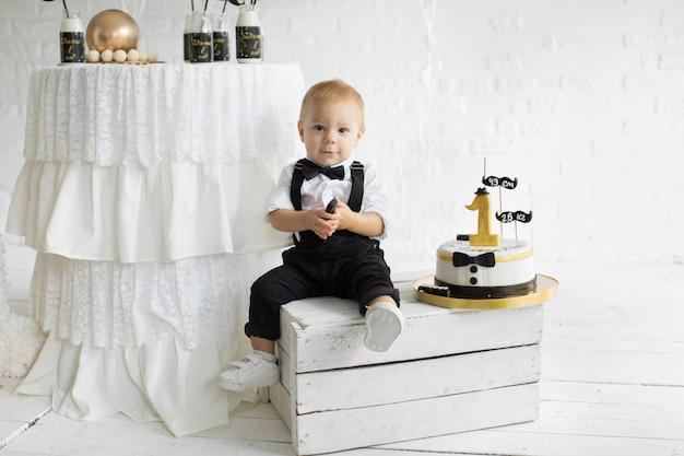 Der erste geburtstag des kindes. ein jahr mit einem kuchen. kind im smoking
