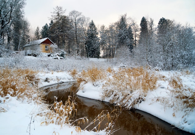 Der erste schnee am ufer des flusses lubya mit einem haus auf dem hügel.
