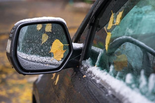 Der erste schnee auf dem spiegel des autos.