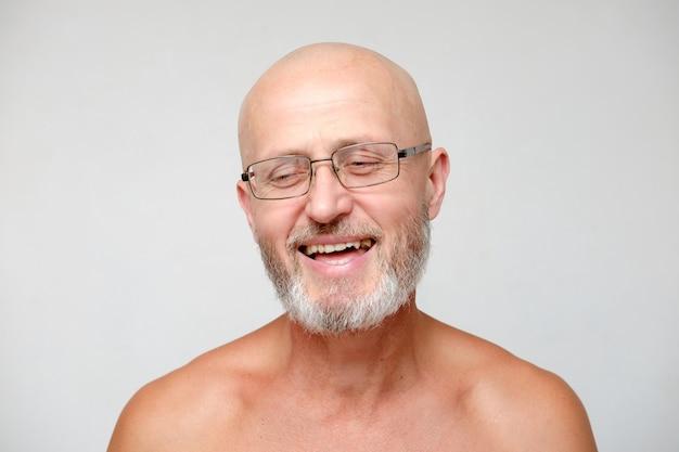 Der erwachsene, der bärtigen mutigen skinhead lacht, ergraute mann in den brillen, lokalisiert auf grau