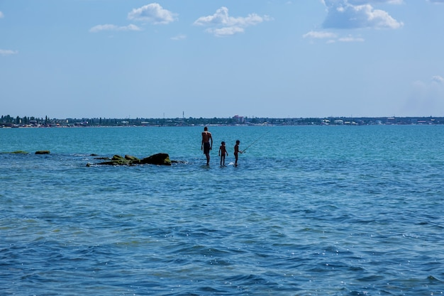 Der erwachsene mann und die kinder angeln stehend auf einem großen steinbedeckten wasser. die leute befinden sich auf einem hintergrund des blauen himmels.