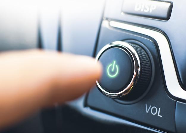 Der fahrer drückt den netzschalter des audioplayers im auto