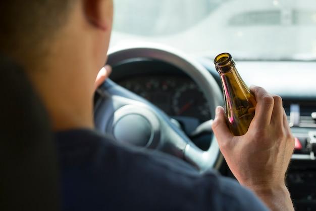 Der fahrer hält beim autofahren eine flasche alkoholisches getränk in der hand.