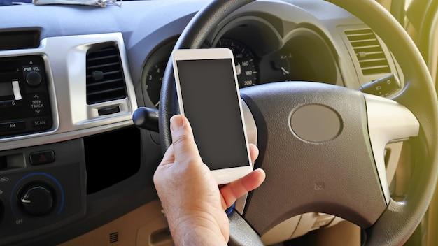 Der fahrer hält smartphone in der hand zwischen der fahrt auf der straße