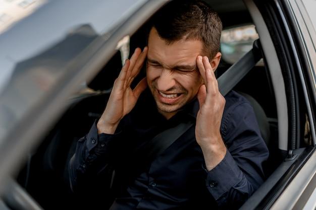 Der fahrer hat sehr starke kopfschmerzen. er ist es leid zu fahren