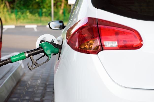 Der fahrer pumpt das benzin des autos an der tankstelle mit kraftstoff. autotank an einer tankstelle.