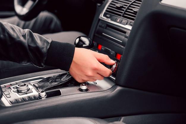 Der fahrer regelt die klimatisierung in seinem stilvollen, modernen auto