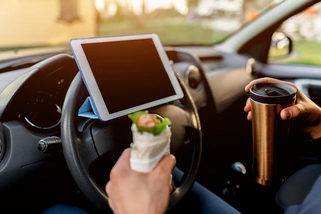 Der fahrer sieht während des mittagessens filme oder fernsehsendungen auf dem tablet. anhalten, um etwas zu essen. mann essen snack im auto und trinkt kaffee oder tee.