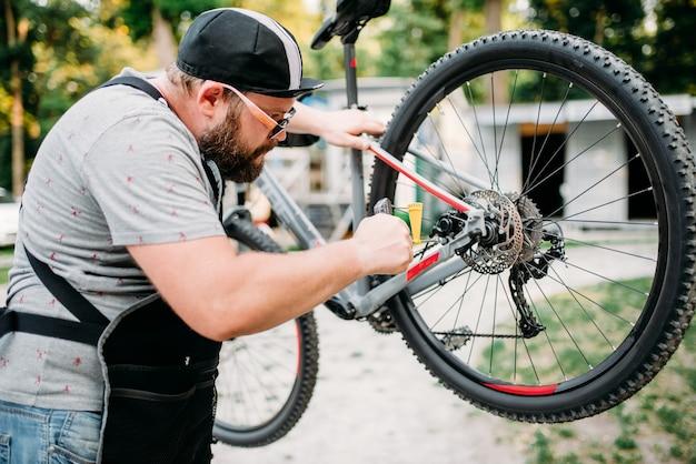 Der fahrradmechaniker in der schürze stellt mit den servicewerkzeugen die scheibenbremsen ein. fahrradwerkstatt im freien