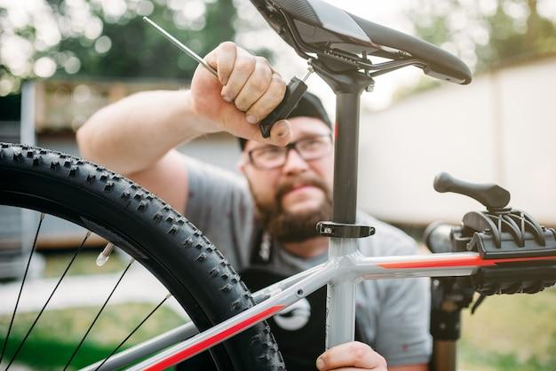 Der fahrradmechaniker stellt den fahrradsitz mit den servicewerkzeugen ein.
