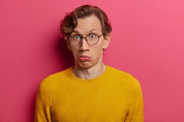 Der fassungslose emotionale kerl spitzt die lippen und sieht verwundert aus, ist verwirrt und überrascht über das hören von informationen, trägt einen gelben pullover und eine transparente brille, isoliert auf einer rosa wand