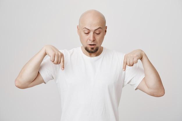 Der faszinierte bärtige erwachsene bärtige mann zeigt nach unten und sieht neugierig aus