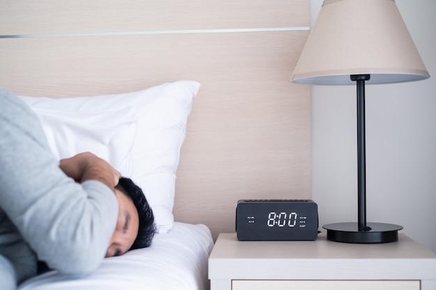 Der faule männliche büroangestellte, der auf bett im schlafzimmer schläft, bedecken sein ohr, um alarmierenden ton des weckers um 8 uhr morgens zu blockieren.
