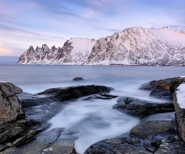 Der felsige strand und die gefrorenen wellen im pool am ersfjord. senja-insel in der region troms in nordnorwegen. langzeitbelichtung