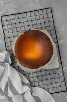 Der fertige san sebastian käsekuchen wird auf einem kühlregal auf grauem betonhintergrund geformt. der prozess der herstellung von san sebastian käsekuchen. rezept schritt für schritt.