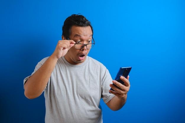 Der fette asiatische typ, der ein graues t-shirt trägt, sieht überrascht von den guten nachrichten, die er von seinem smartphone erhalten hat. männer zeigen geschockte bewegungen mit hervortretenden augen beim herunterrollen der brille auf einem smartphone