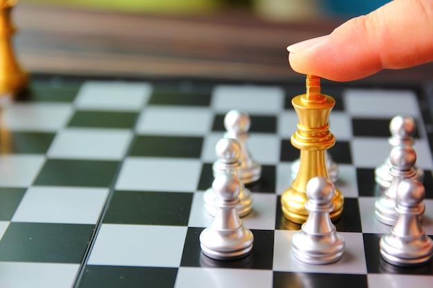 Der finger auf goldenem königsschach zwischen silbernem schach auf schachbrett