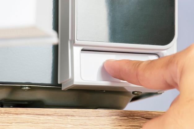 Der finger drückt einen knopf, um die tür der mikrowelle zu öffnen