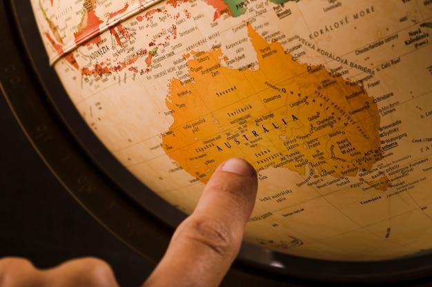 Der finger einer person, der auf australien-land auf kugel zeigt