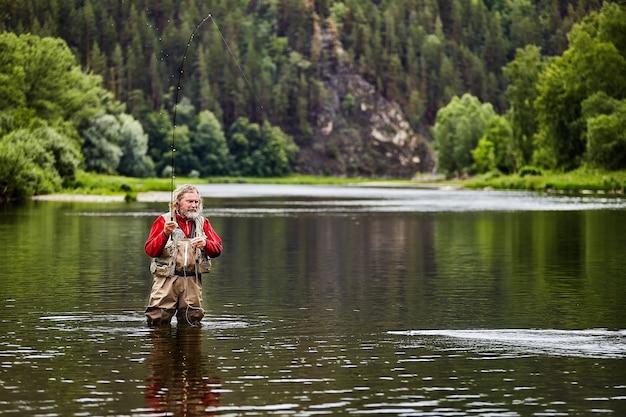 Der fischer fängt fische durch fliegenfischen oder werfen.