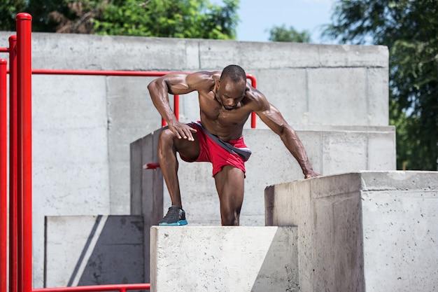 Der fitte athlet macht übungen. afro oder afroamerikanermann im freien an der stadt. sportübungen hochziehen.